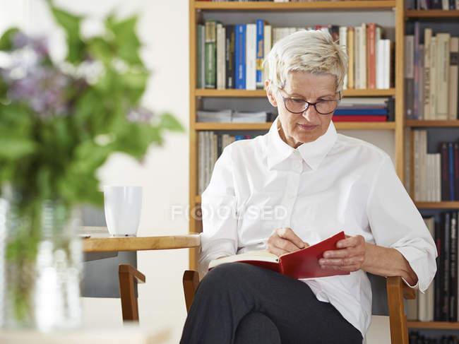 Старшая женщина, пишущая дома в блокноте — стоковое фото