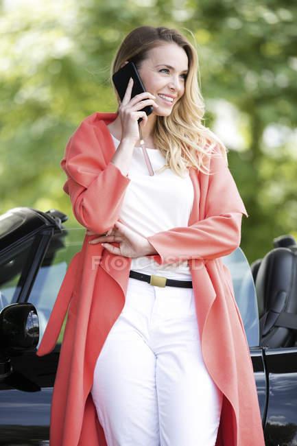 Portrait de femme blonde souriante téléphonant avec smartphone devant une voiture de sport noire — Photo de stock