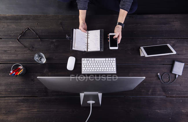 Man working at desk with computer and various digital gadgets, updating personal organizer — Stock Photo