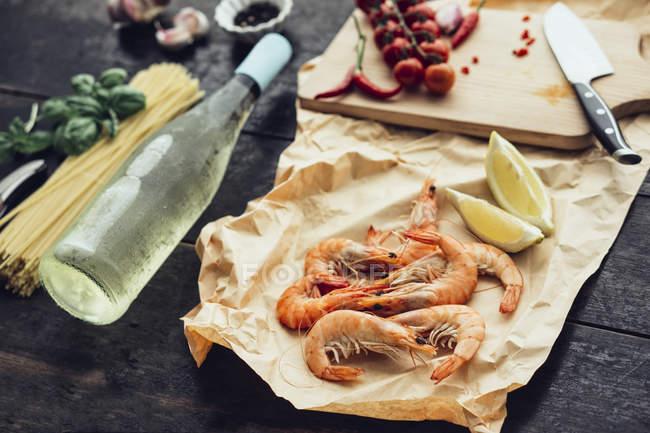 Ingredientes para plato de pasta con gambas, tomates y vino blanco - foto de stock