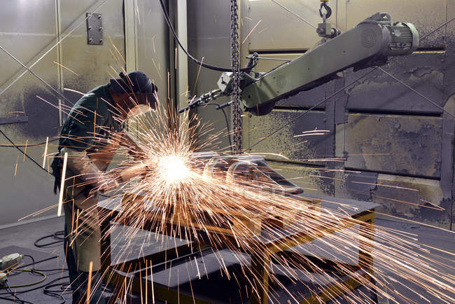 Man Working with grinding machine in a foundry — Stock Photo