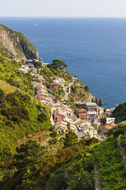 Italy, Cinque Terre, View of Riomaggiore on hill over water — Stock Photo