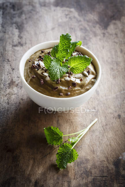 Closeup of smoothie bowl with cocoa, avocado and green melissa branch on wooden table — Stock Photo
