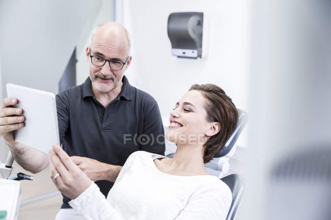 Dentist consulting woman showing at tablet — Stock Photo