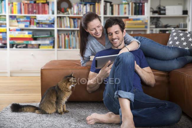 Erwachsenes Paar auf Sofa liegend, mit digitalem Tablet — Stockfoto