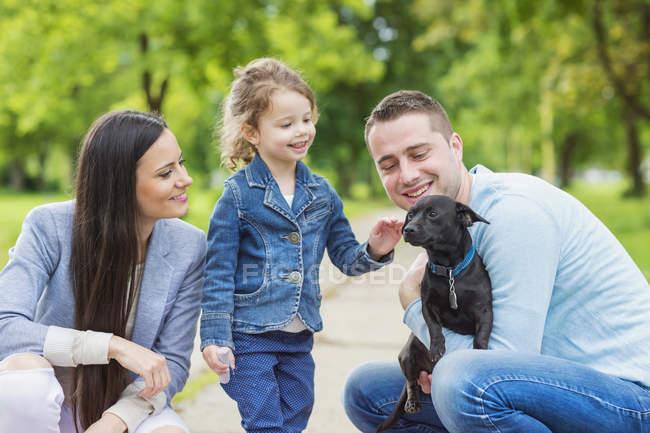 Famiglia felice giocare con il cane nel parco — Foto stock