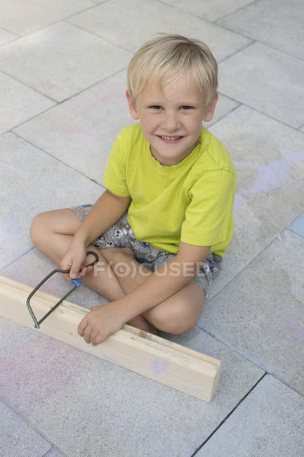 Little boy with saw and wooden bar sitting on floor — Stock Photo