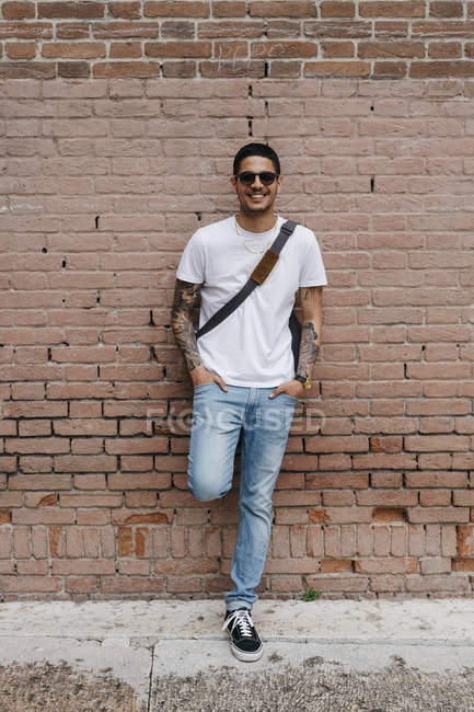 Smiling young man leaning against a brick wall — Stock Photo
