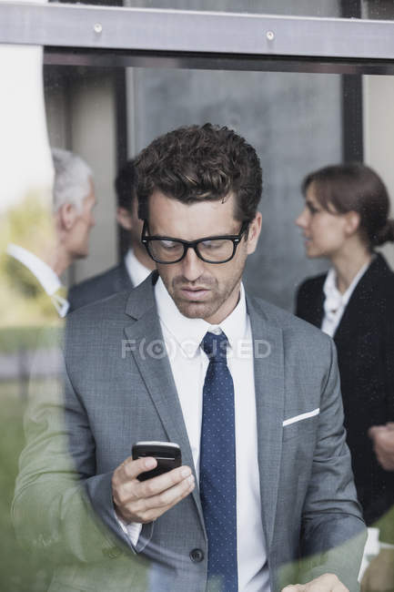 Caucasian businessman looking at cell phone — Stock Photo