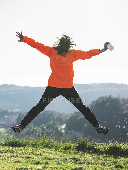 Jeune jogger femme sautant en l'air — Photo de stock