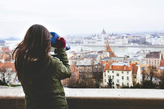 Ungarn, Budapest, Frau, die durch ein Fernglas auf das Parlamentsgebäude von Castle Hill — Stockfoto