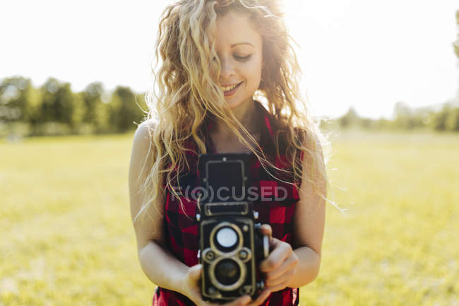 Smiling woman with retro camera  in nature — Stock Photo