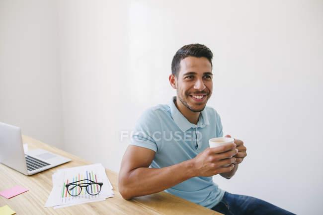 Jovem bebendo café na mesa no escritório — Fotografia de Stock