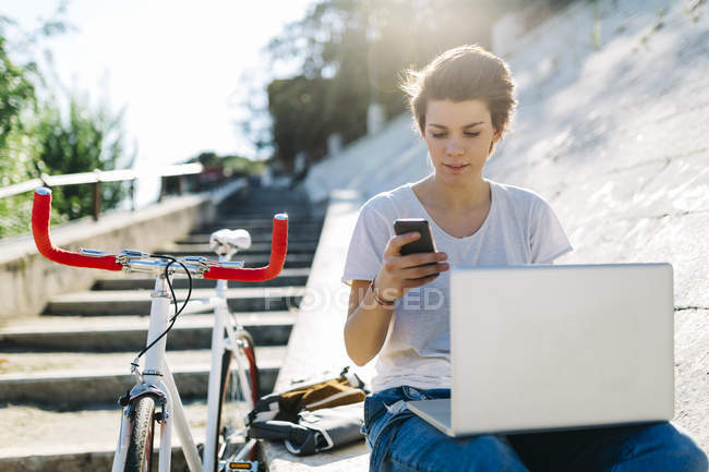 Young woman with bicycle sitting outdoors using laptop and cell phone — Stock Photo