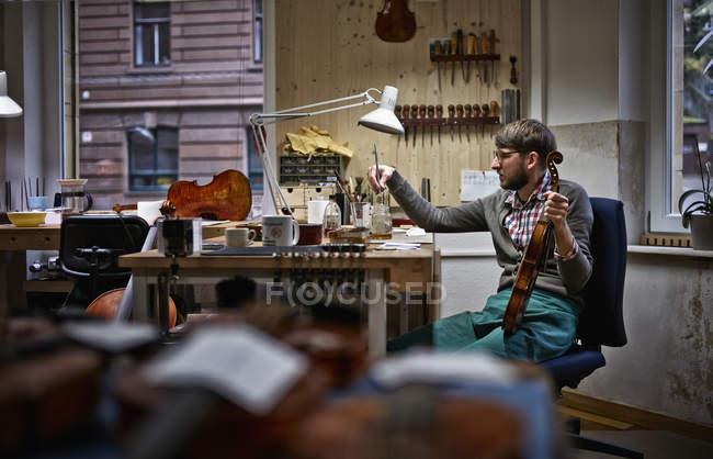 Geigenbauer Lackierung repariert Violine in Werkstatt — Stockfoto