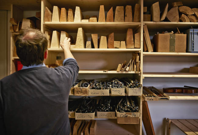 Violin maker choosing wooden material in workshop — Stock Photo