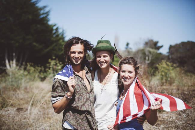 Портрет трех улыбающихся хиппи с флагом США в природе — стоковое фото