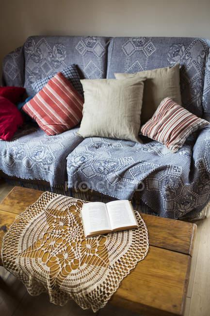 Sofá com almofadas e guardanapo na mesa de café — Fotografia de Stock