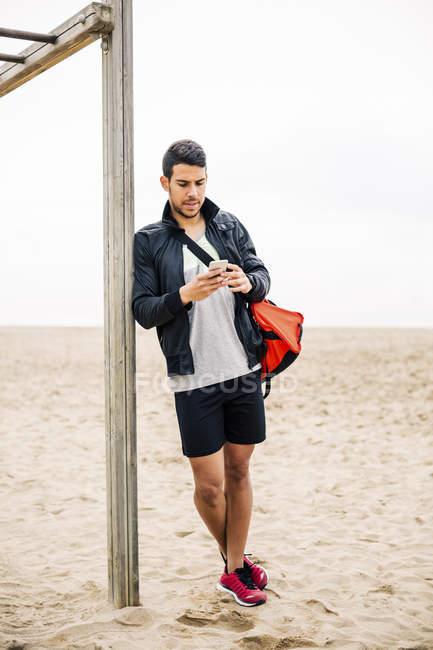 Jovem homem desportivo usando telefone celular na praia arenosa — Fotografia de Stock