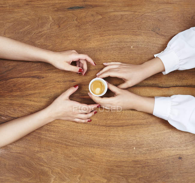Hands with espresso cup on wooden surface — Stock Photo