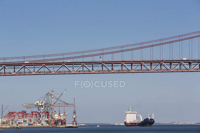 Portugal, Lisbon, View of 25 de Abril Bridge at River Tagus and city harbor — Stock Photo
