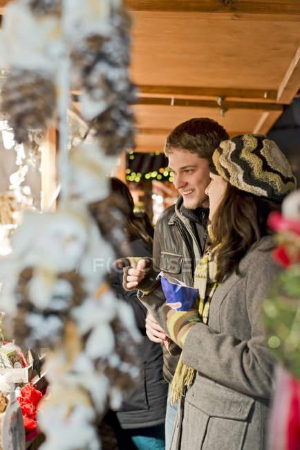 Германия, Берлин, молодые пары смотрят предложения на Рождественском рынке — стоковое фото