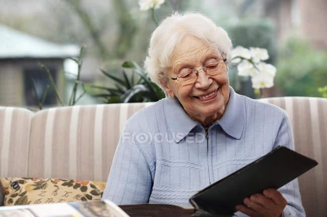 Smiling senior woman watching old photographs at home — Stock Photo