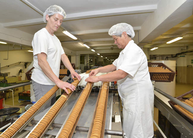 Two women controlling cookies on production line in a baking factory — Stock Photo