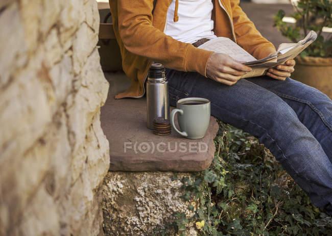 Giovane seduto su gradini con pausa caffè, vista parziale — Foto stock