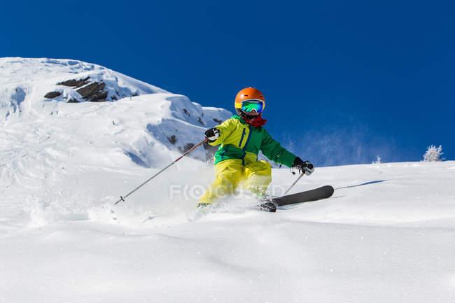 Мальчик в шлем и горнолыжная одежда для катания в Солнечный день на снежном склоне — стоковое фото