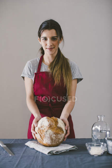 Женщина, держащая домашнего хлеба каравай на кухонное полотенце — стоковое фото