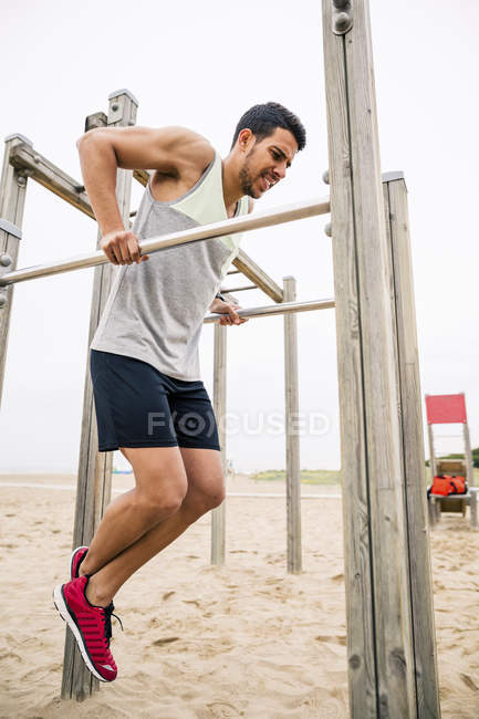 Young man exercising on bars on beach — Stock Photo