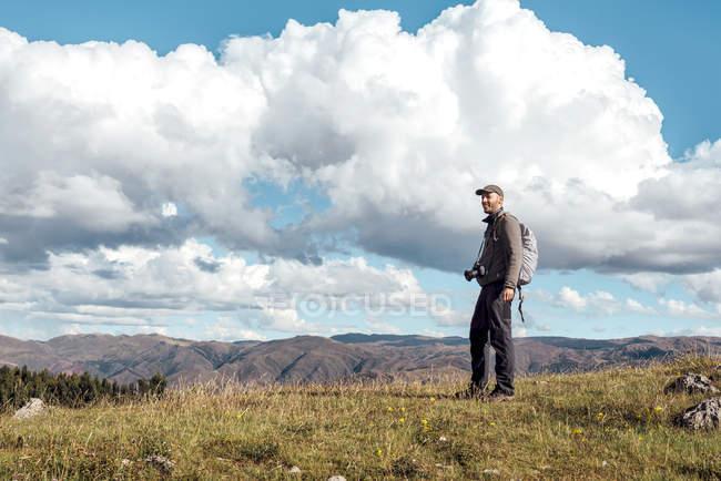 Perù, Cusco, escursionismo uomo con la macchina fotografica e zaino in piedi sulla montagna — Foto stock