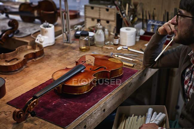 Violin maker sitting at workbench in workshop — Stock Photo