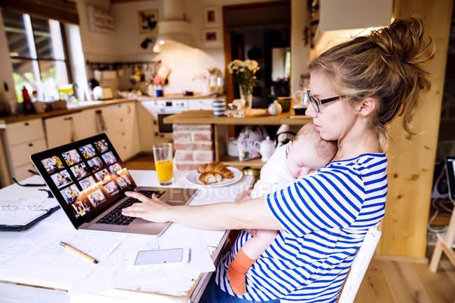 Mutter mit Baby zu Hause arbeitet mit Laptop — Stockfoto