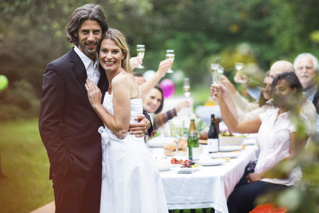 Portrait of Bride and groom standing on a garden party — Stock Photo