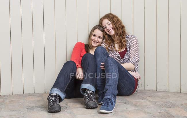Портрет молодих жінок, притулившись дощаті стіни, посміхаючись — стокове фото