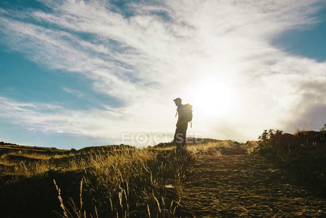 Siluetta di Perù, isola di Amantani, dell'uomo con lo zaino escursionismo al tramonto — Foto stock