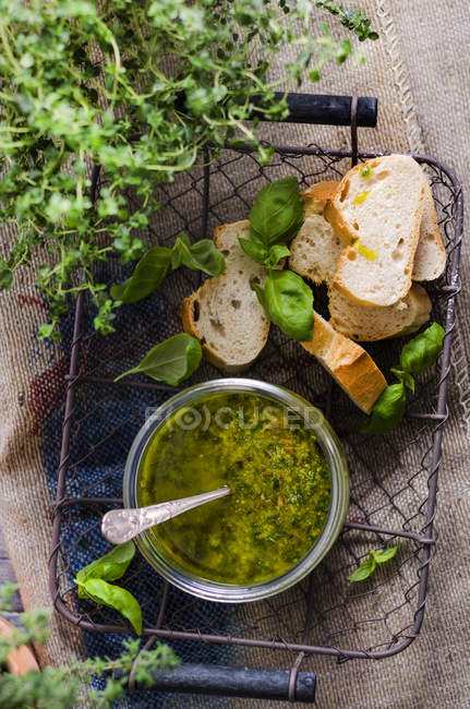 Fresh basil pesto in a glass and slices of baguette in a basket, top view — стокове фото