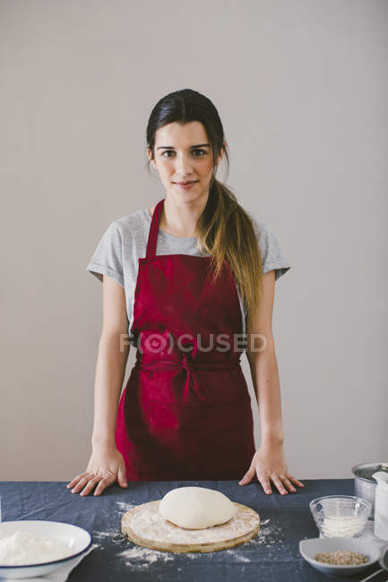 Woman standing next to table with bread dough and looking at camera — Stock Photo