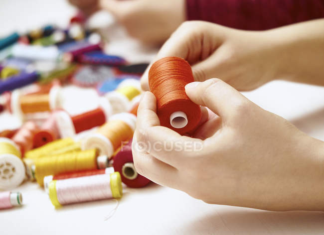 Female hands holding cotton reel — Stock Photo