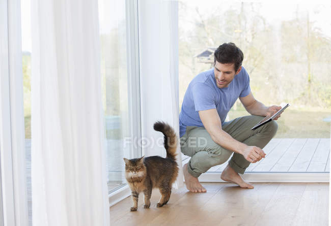 Man with digital tablet looking at cat — Stock Photo