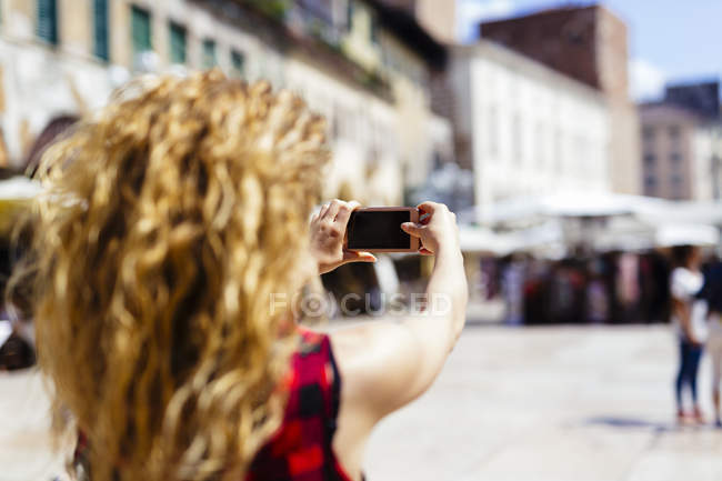 Italy, Verona, woman taking a cell phone picture in the city — Stock Photo