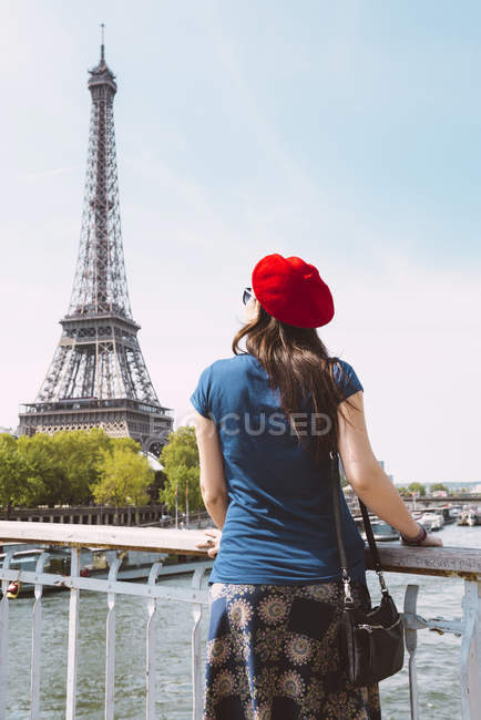 France, Paris, back view of woman wearing red beret looking at Eiffel Tower — Stock Photo