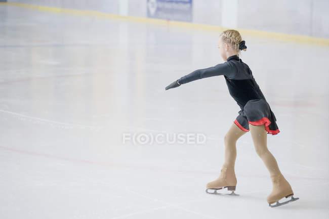 Jovem patinadora feminina se movendo na pista de gelo na competição — Fotografia de Stock
