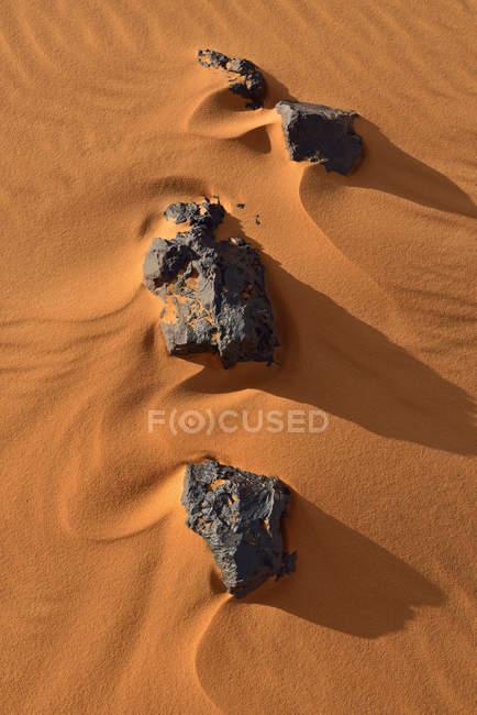 Algérie, Tassili n Ajjer, Sahara, rochers et ondulations sur une dune désertique pendant la journée — Photo de stock