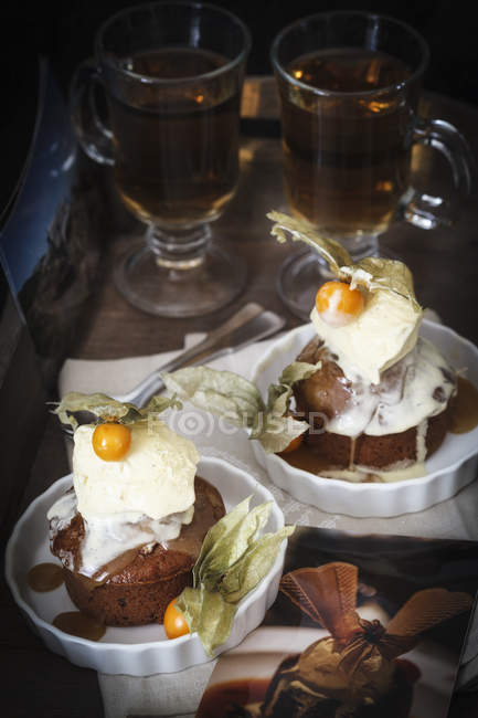 Sticky toffee pudding with vanilla ice cream, physalis and tea in background — Stock Photo