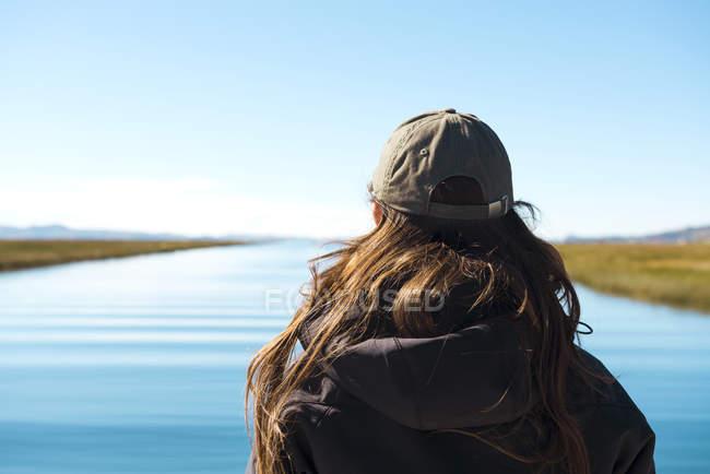 Перу, Пуно, Женщина, смотрящая на озеро Титикака — стоковое фото