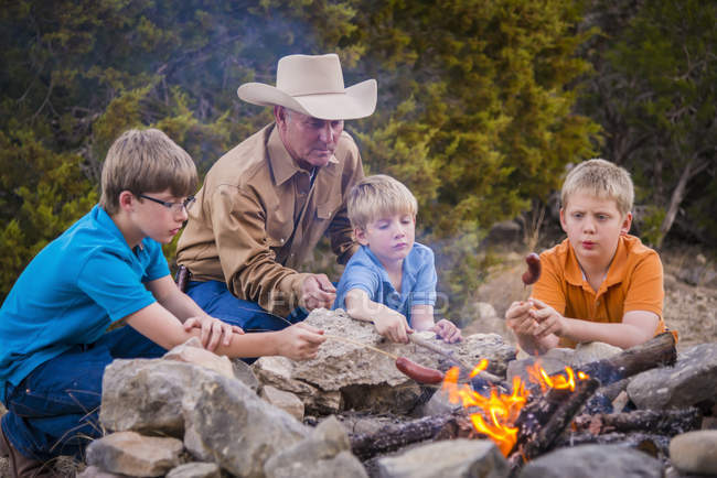 Father and sons roasting sausages over camp fire — Stock Photo