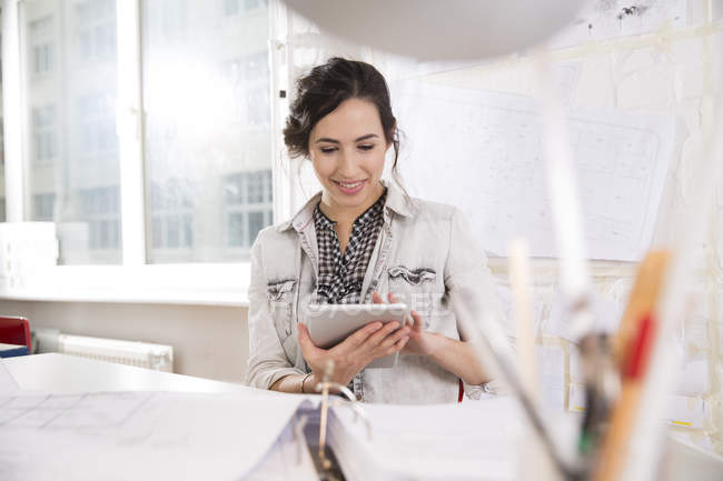 Portrait of young female architect with digital tablet at her desktop in office — Stock Photo
